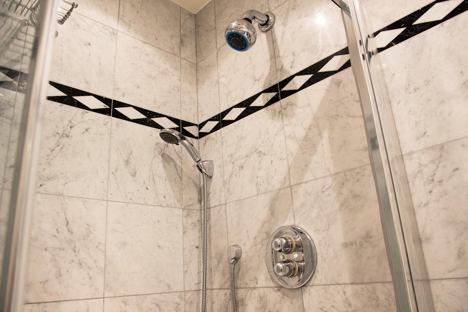 The large shower in bathroom 1 features both fixed and flexible shower heads.