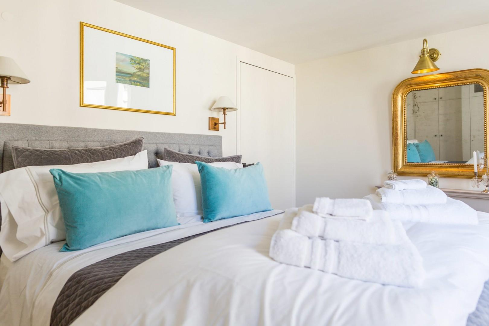 Relax in the stylish bedroom with a comfortable bed and en suite bathroom.