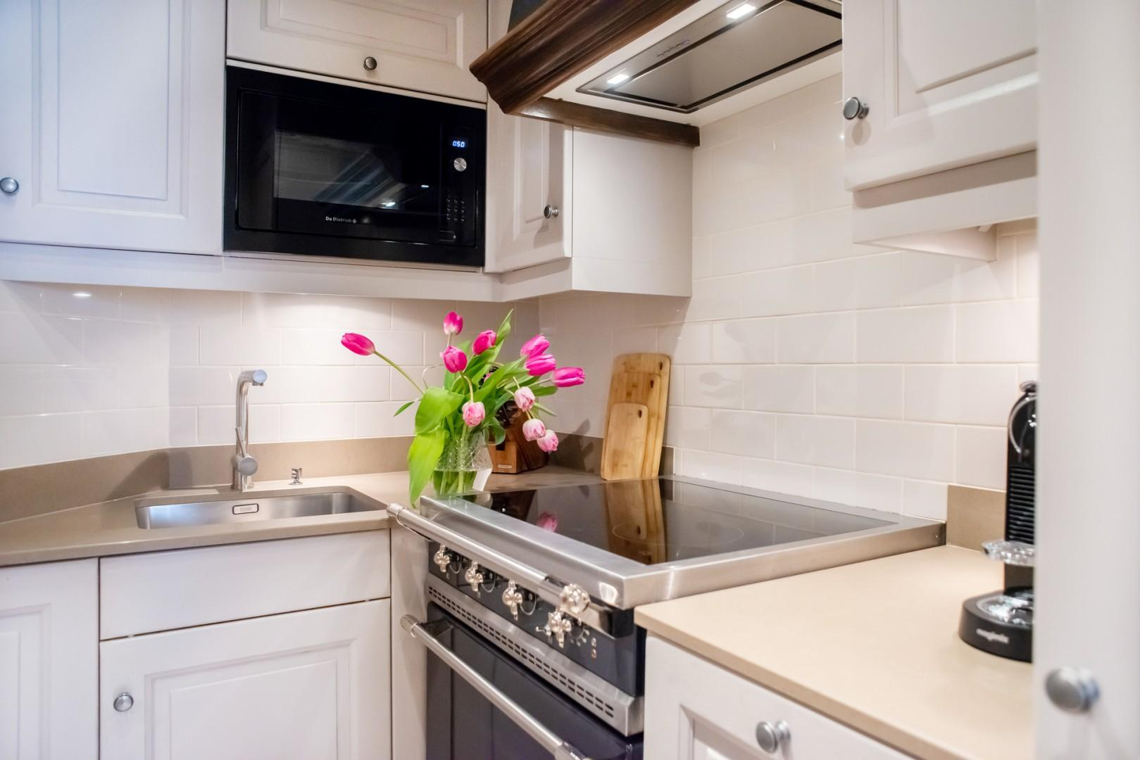 Enjoy preparing meals in this modern kitchen with a premium Lacanche range.