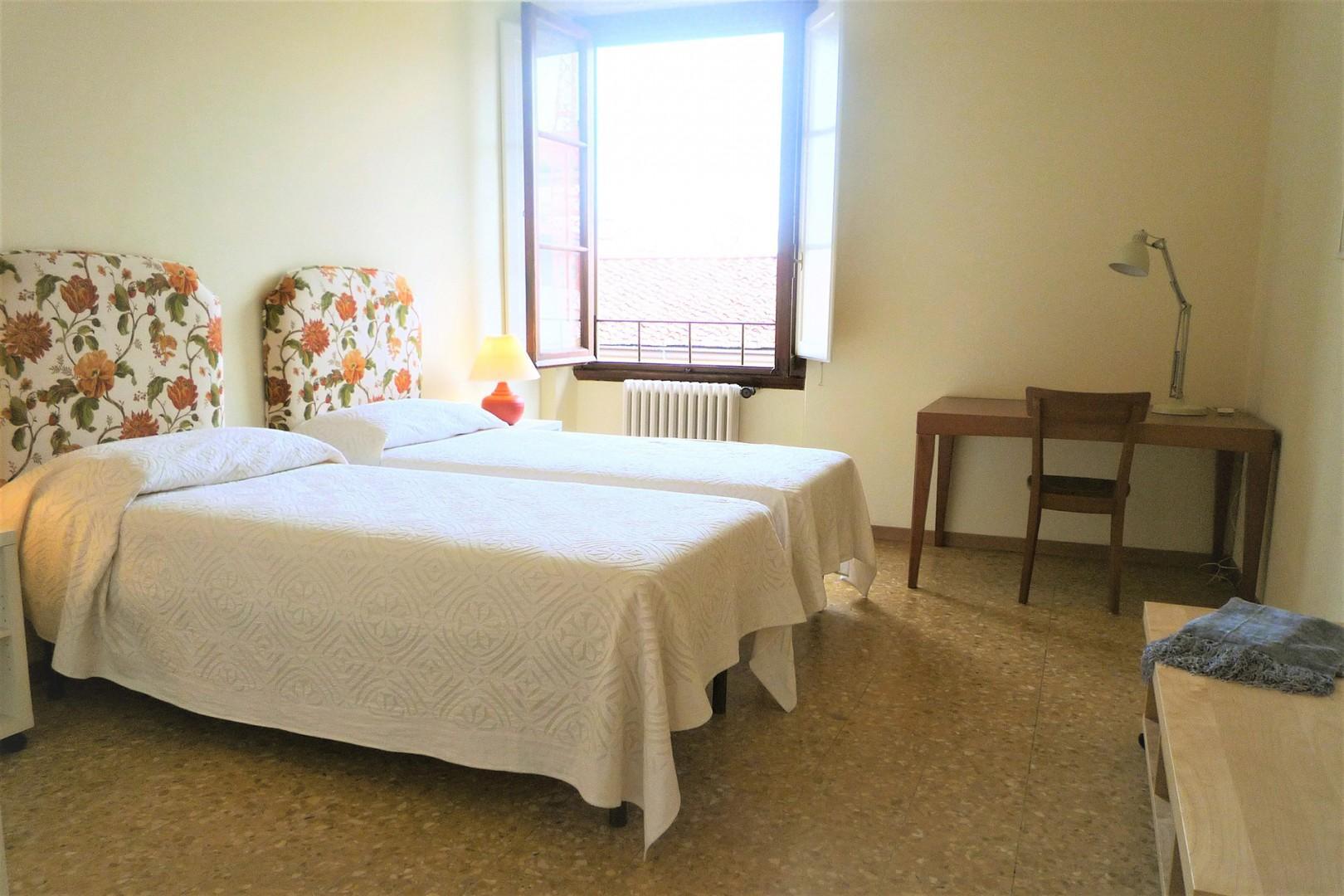 Bedroom 2 has two beds. The window overlooks the street.