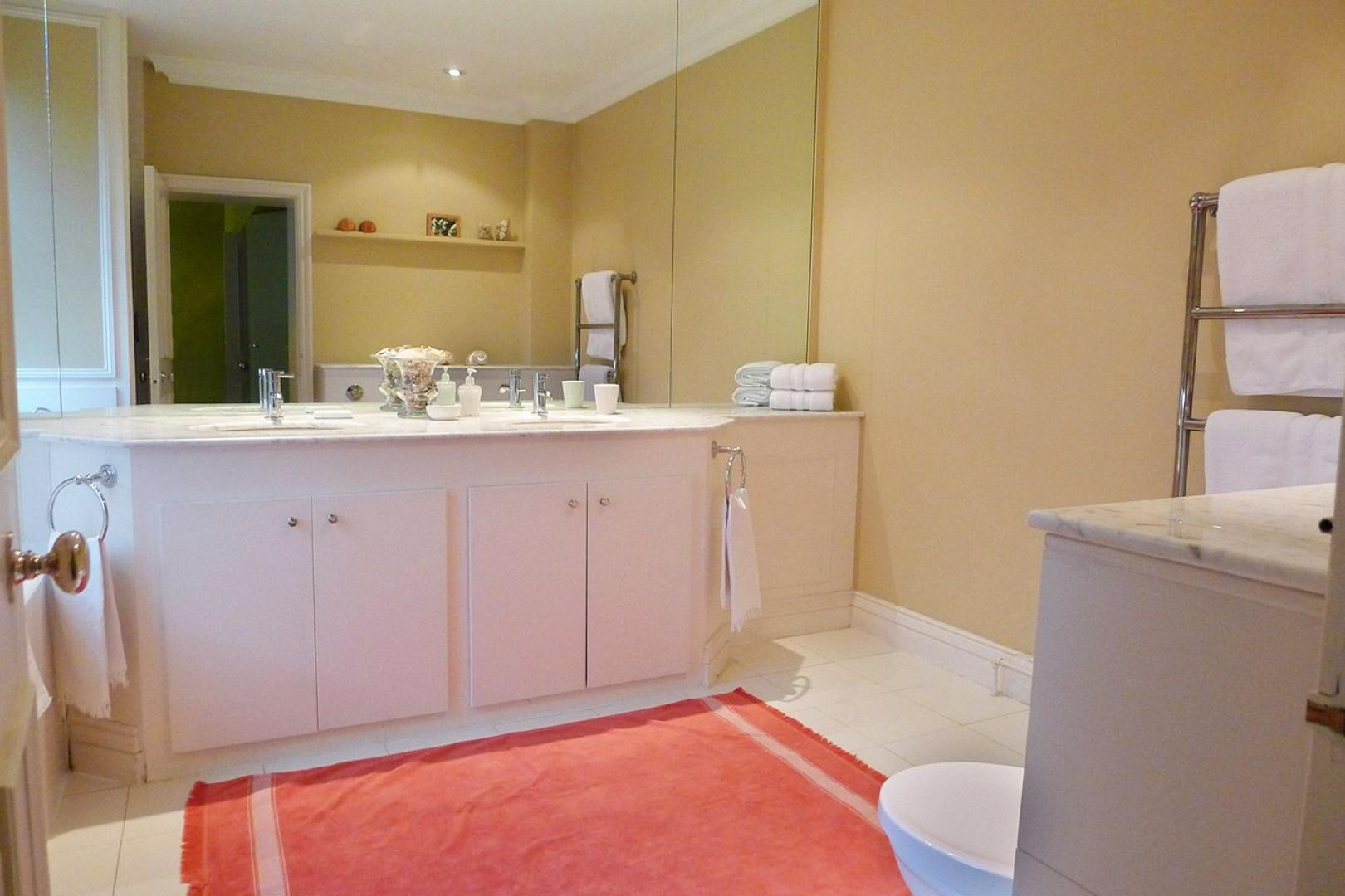 En suite with bathtub, shower, toilet and double sink