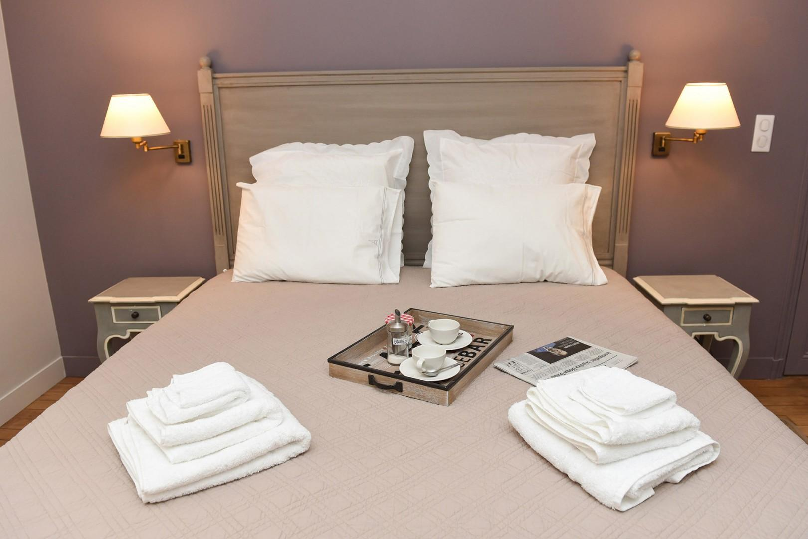 Relax in the comfortable bed after a fun day of sightseeing in Paris.