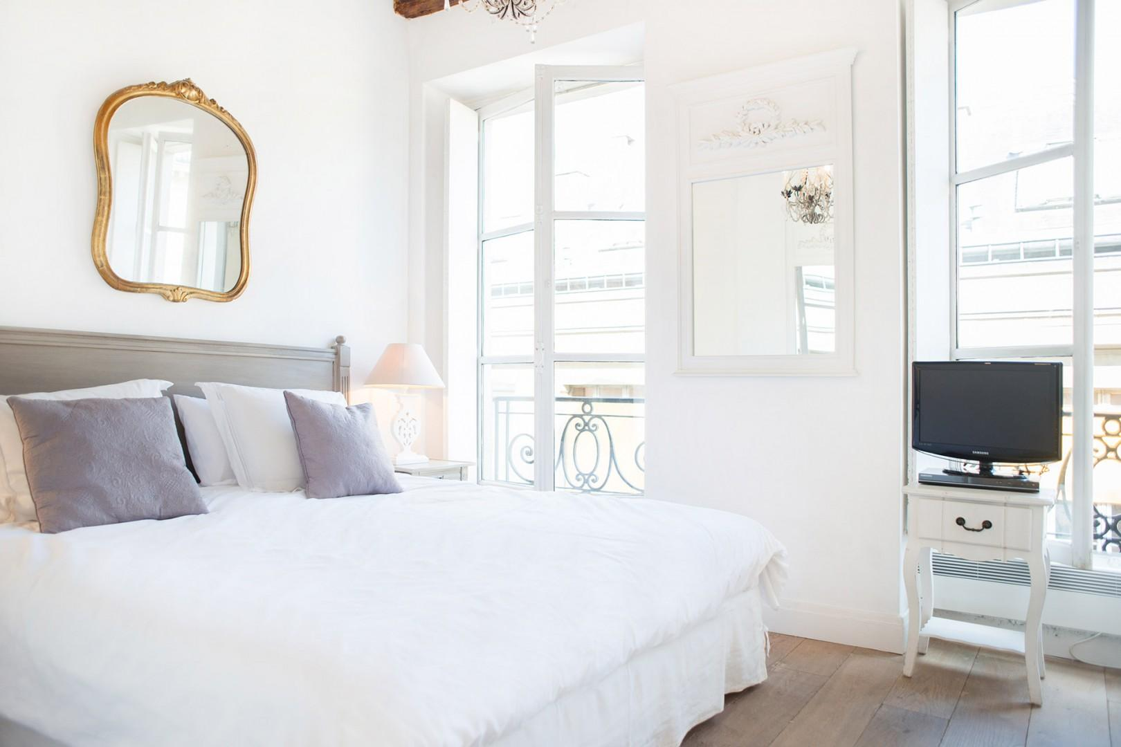 Relax in the spacious, bright bedroom with a large bed.