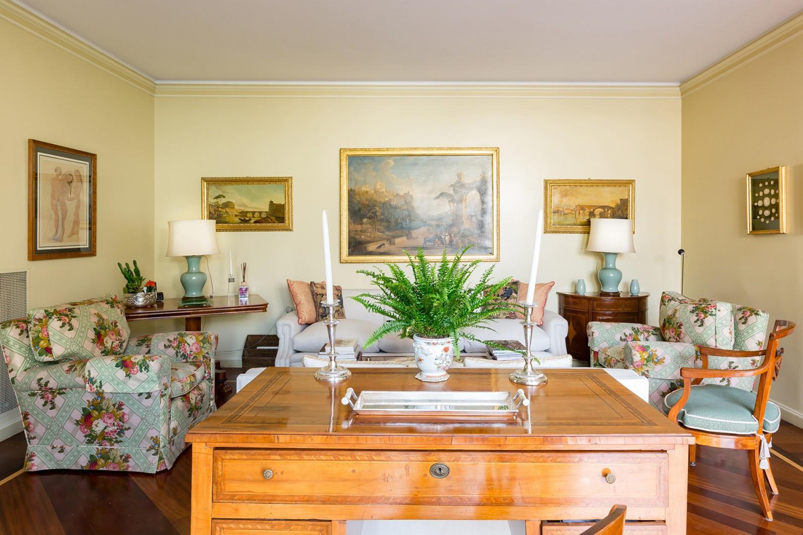 Fine oil paintings of Rome and the Roman countryside decorate the walls of the sunny living room.