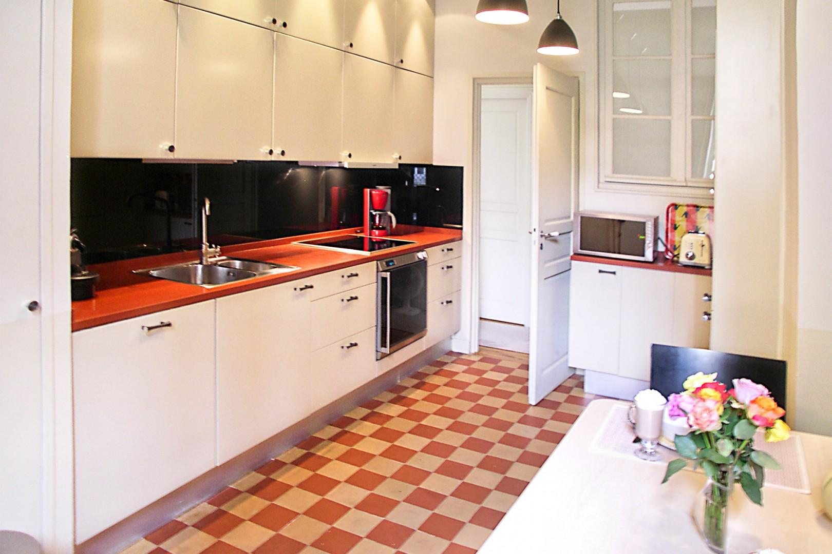 Enjoy cooking in this elegant kitchen with stylish checkerboard tiles.