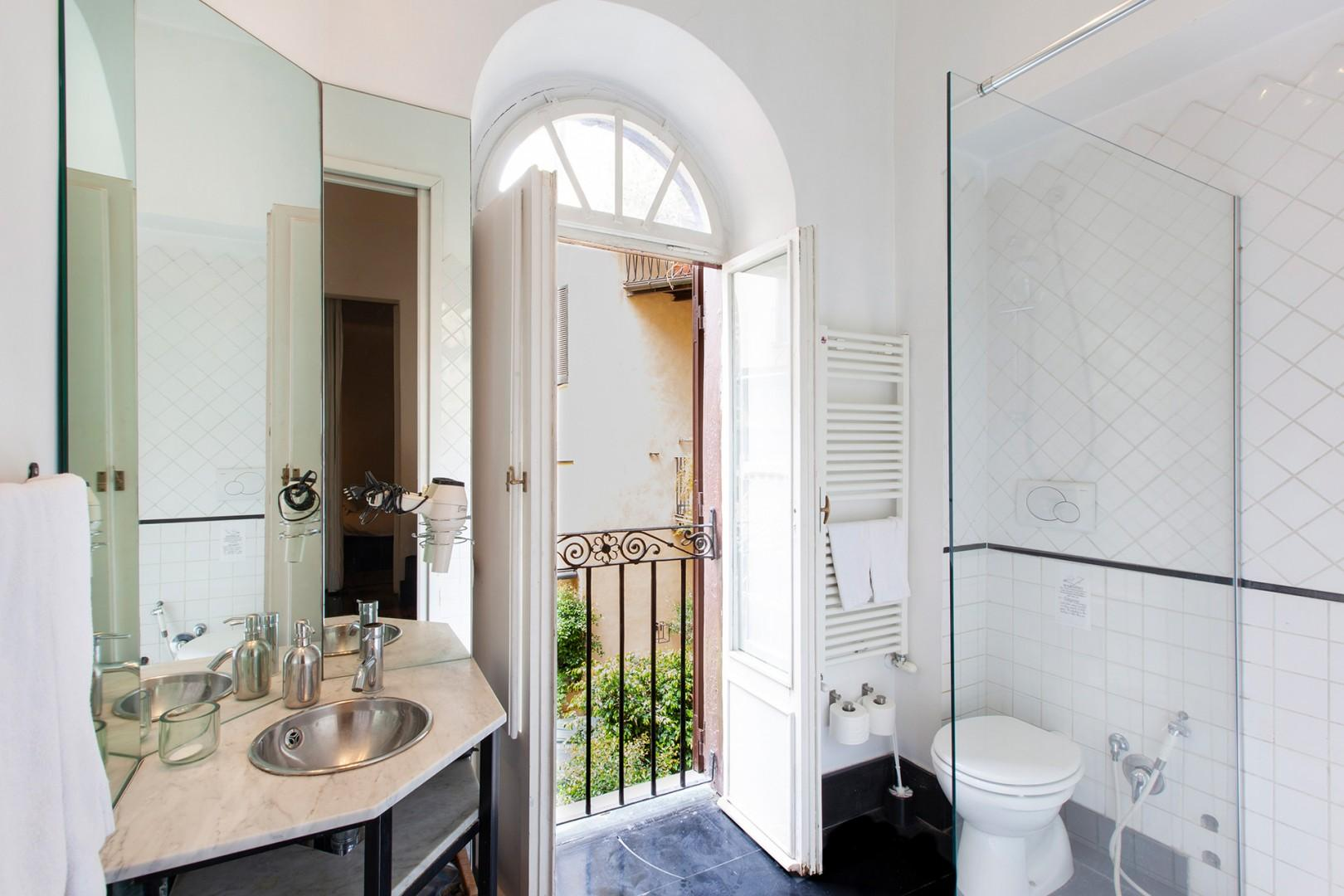 This sparkling bathroom has a modern sink mounted on a glass counter.