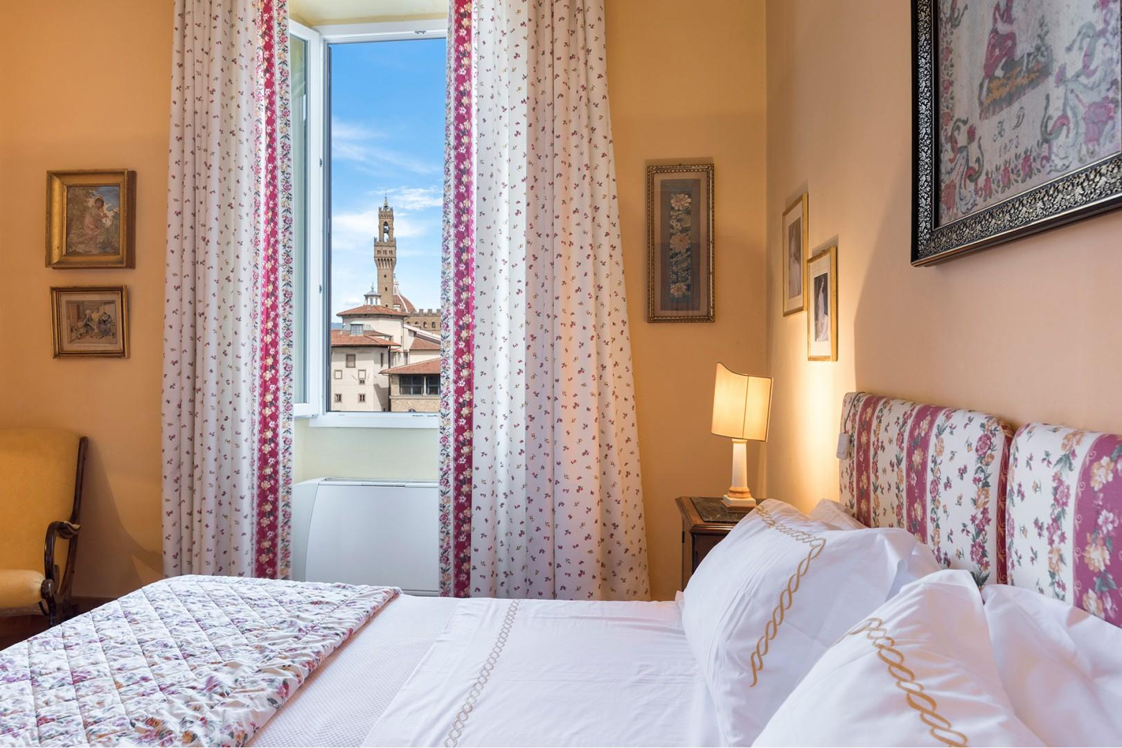Sunny bedroom 1 has gorgeous Arno River views. See the bell tower of Palazzo Vecchio in this photo.