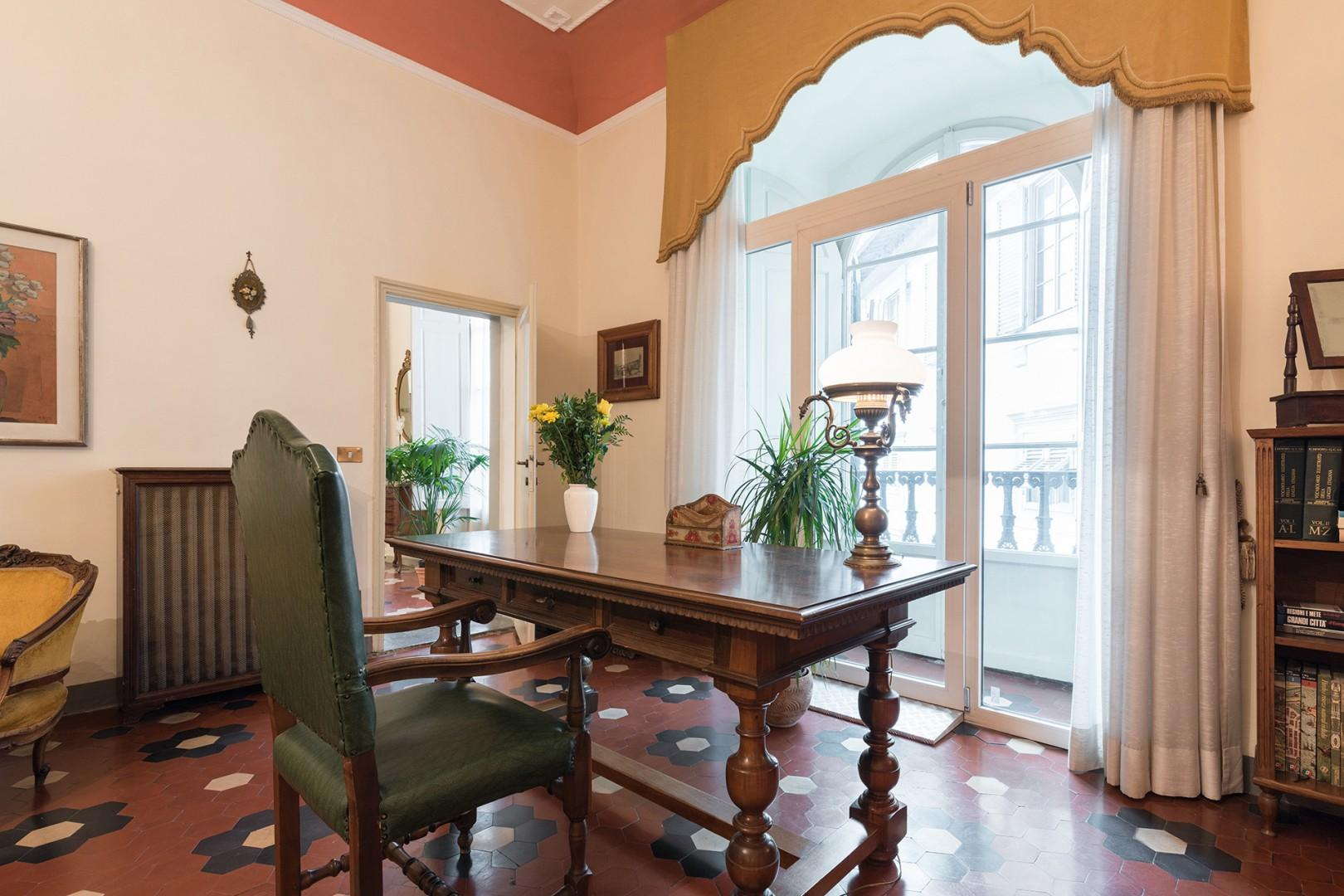 Antique writing desk in bedroom in front of bright window.