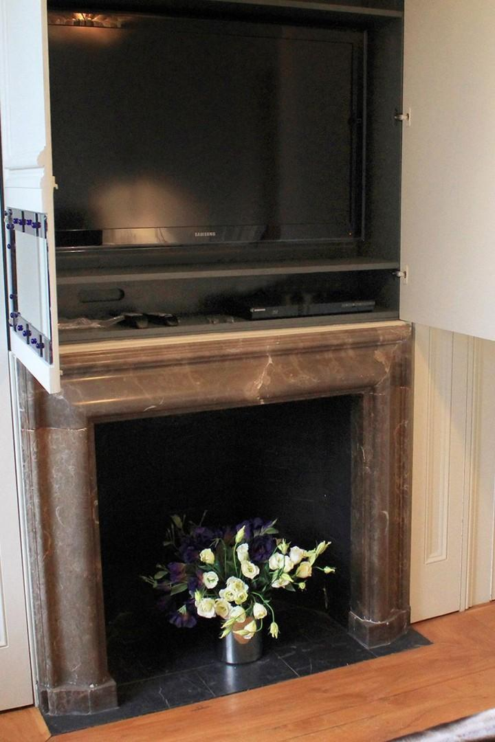 Large flat screen TV located behind cupboards in bedroom