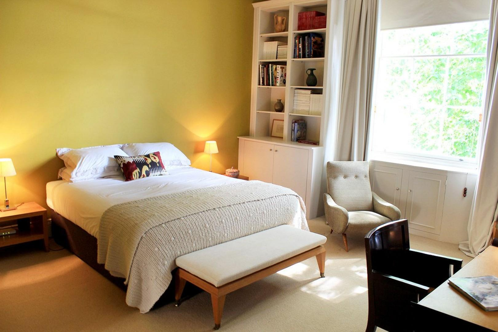 Gorgeous bedroom 1 with comfortable bed and cozy armchair