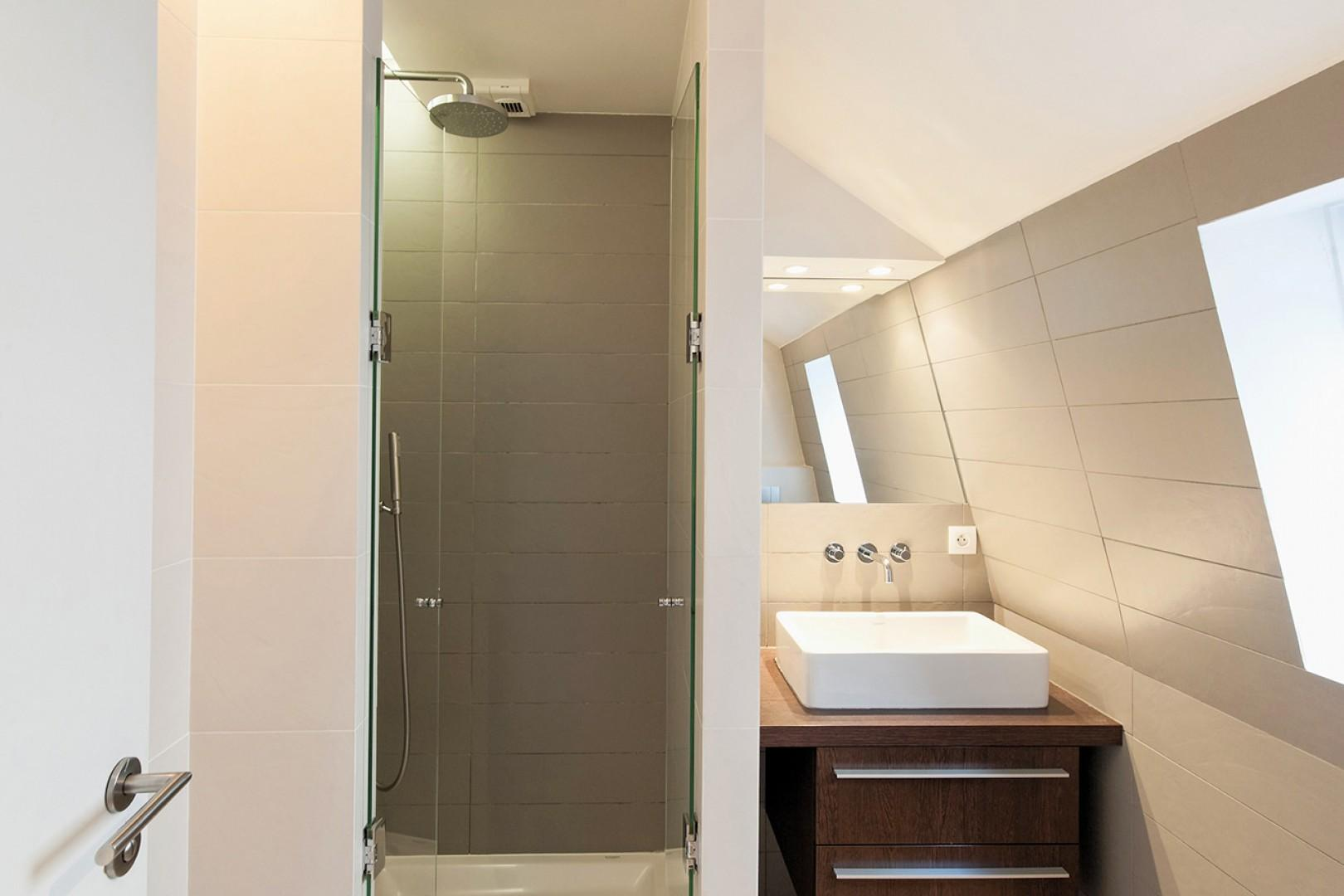 The bathroom is equipped with a shower, sink and toilet.