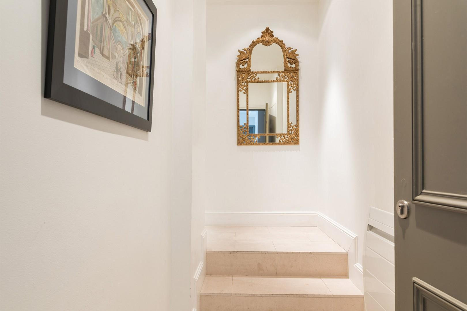 A Belle Epoque-styled mirror decorates the entryway.