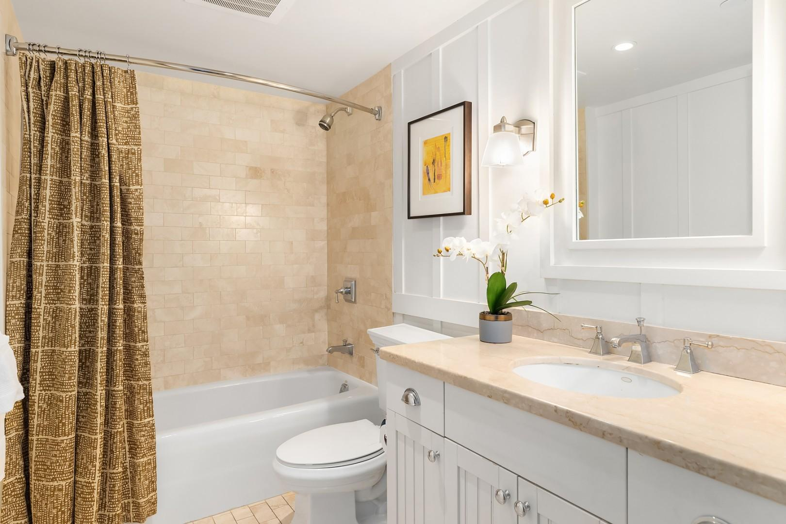 Full guest bath with tub adjacent to the first bedroom.