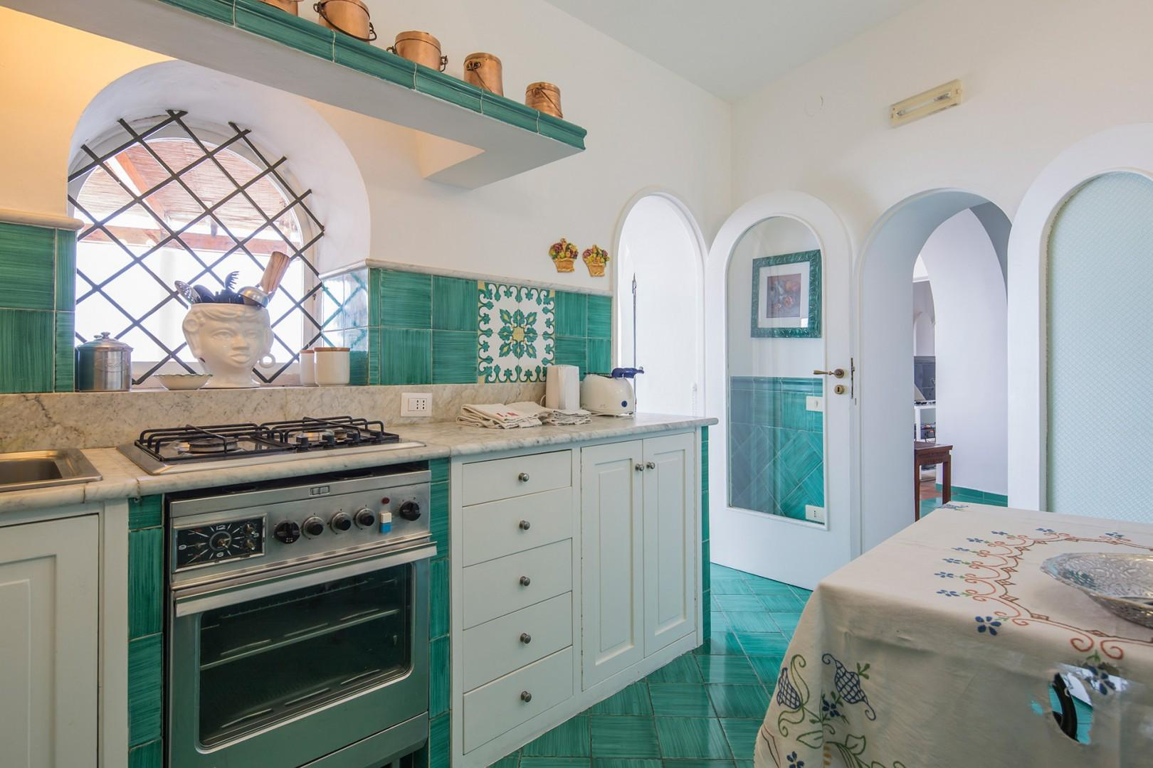 Pretty turquoise tiles carry throughout the dining and fully equipped kitchen.