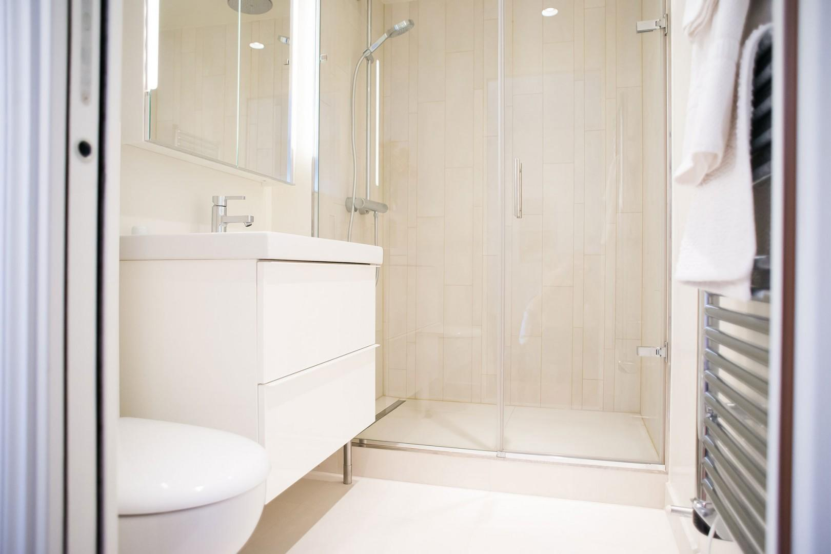 The luxurious en suite bathroom has a shower, sink and toilet.