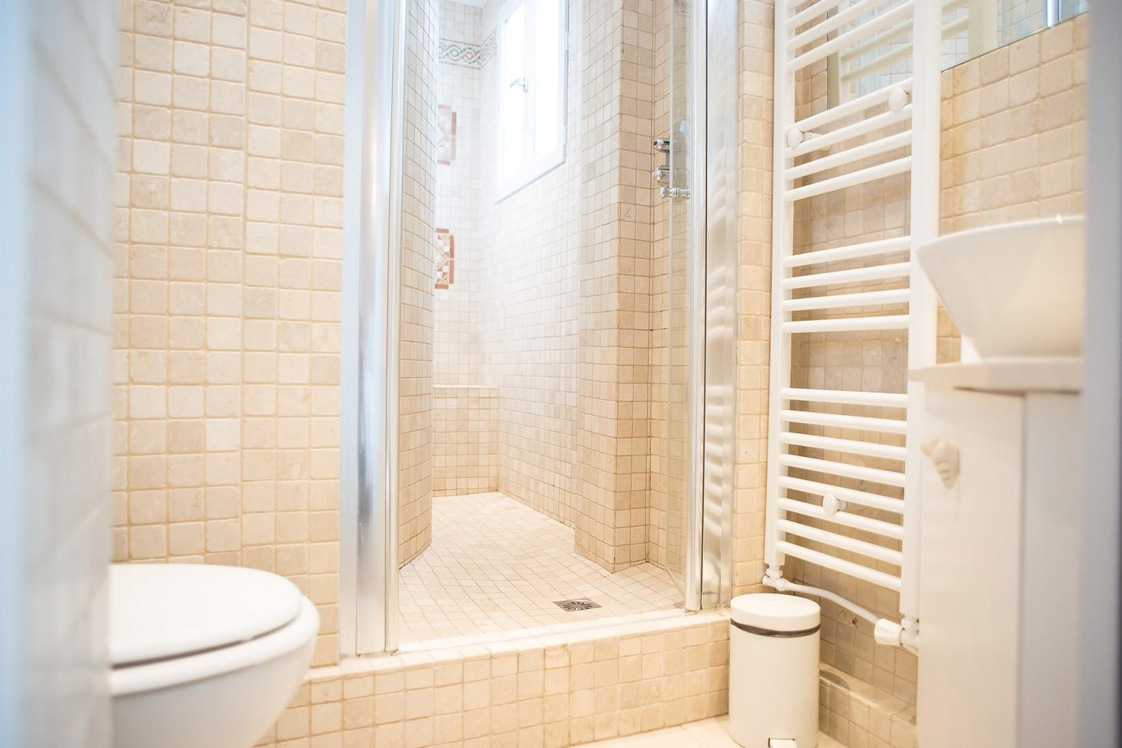 The luxurious en suite bathroom has a shower, toilet and sink.