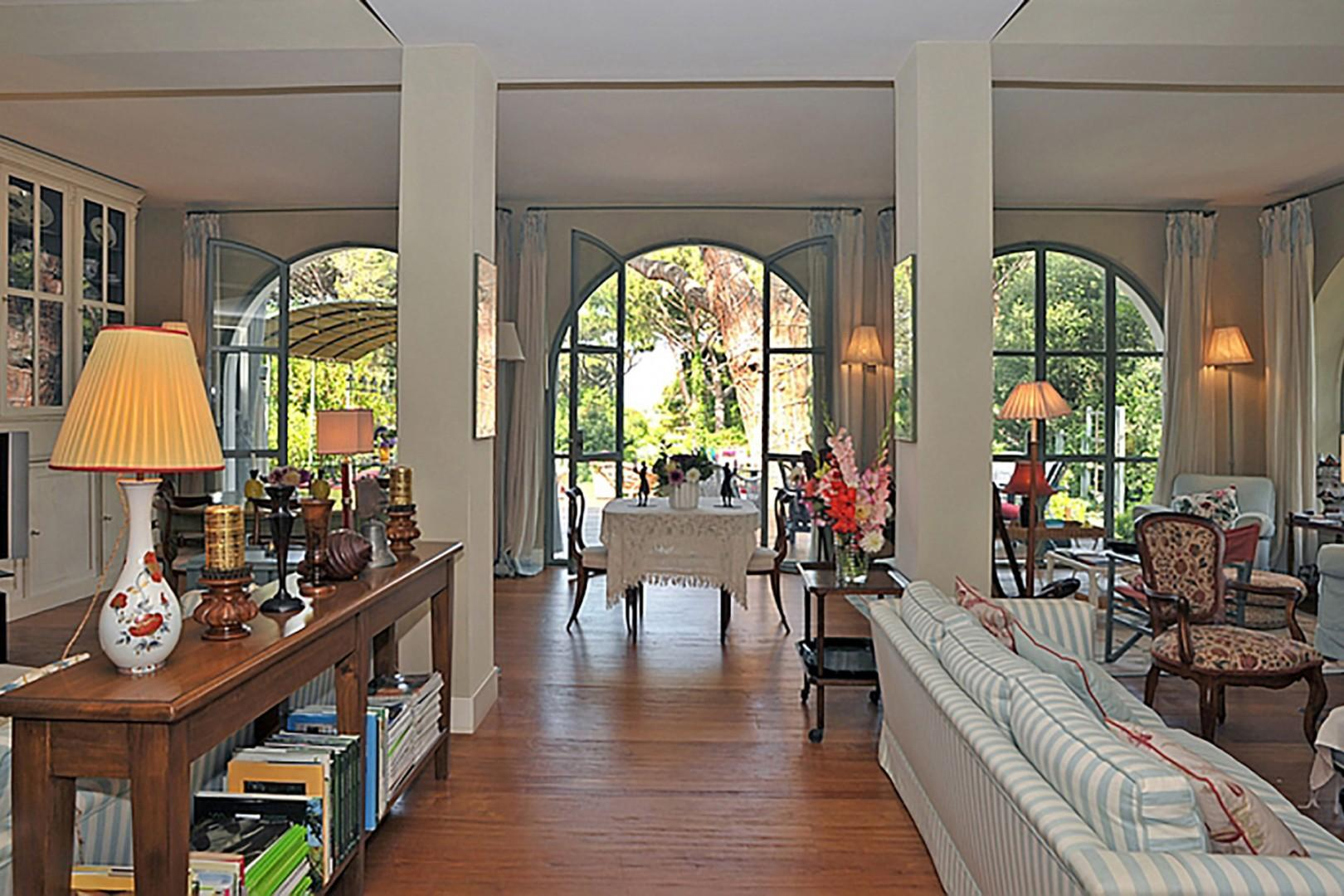 Gracefully arched windows on two sides of the living room bring the outside in.