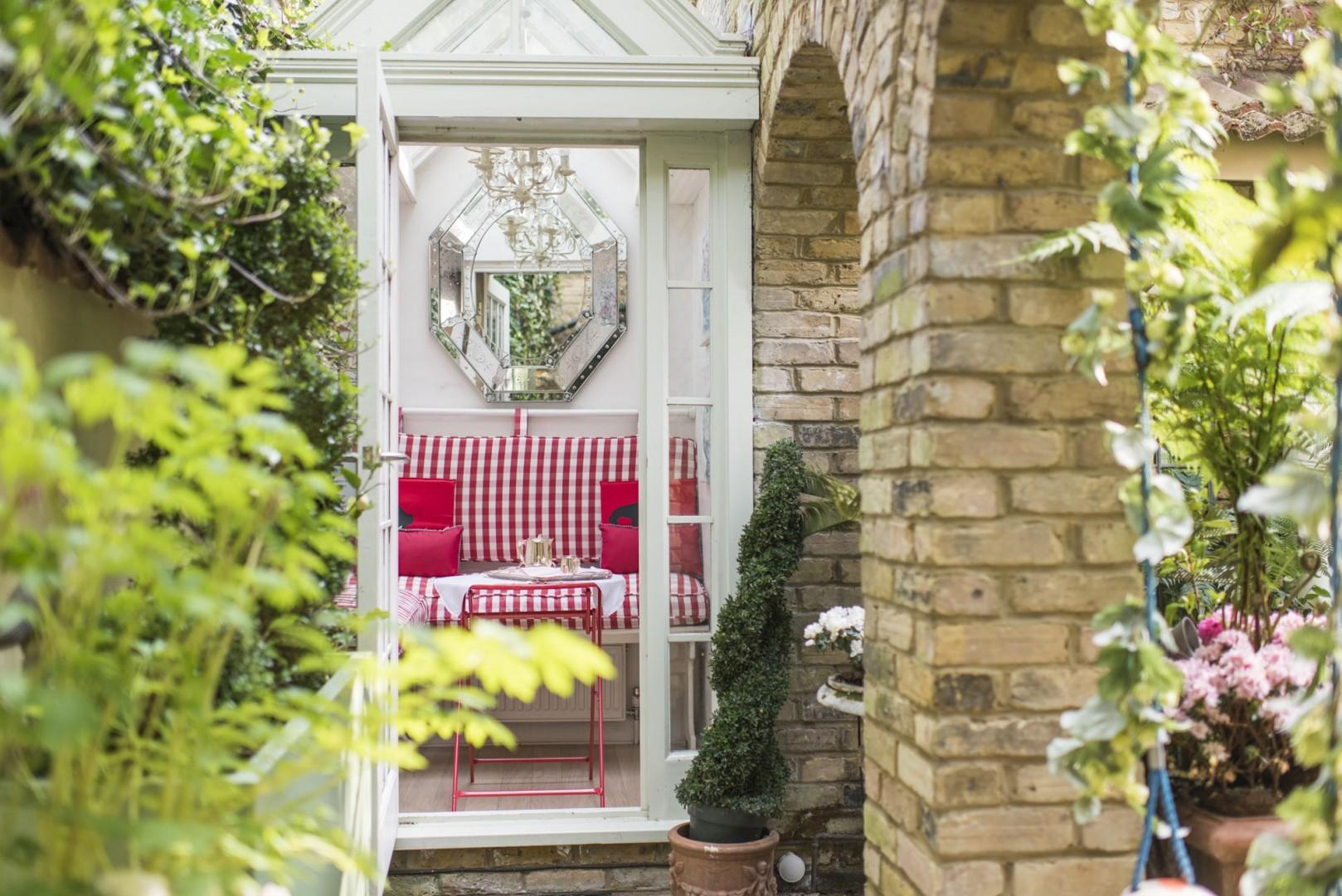 The door to the garden looks directly onto the delightful glass conservatory with chairs and table