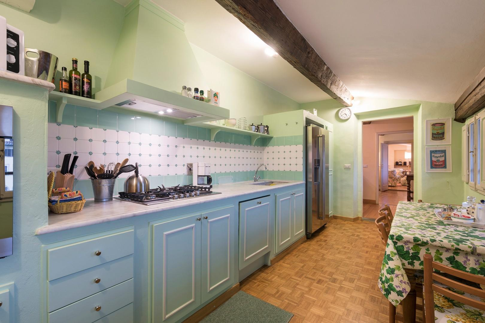 Kitchen is bright and cheerful and fully equipped with pots, pans, dishes.