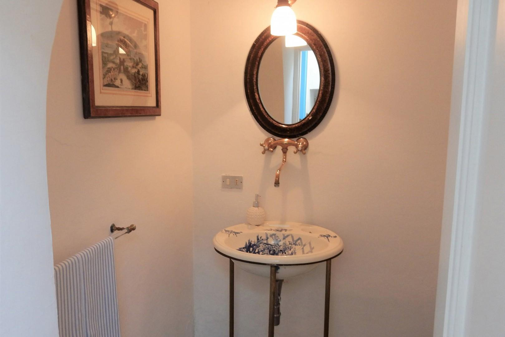 Half bath on the staircase landing has a toilet and sink.