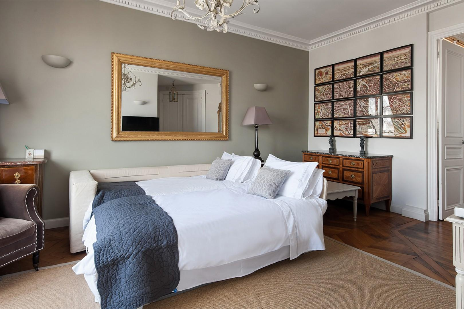 The living room is equipped with a high-quality sofa which converts into extra sleeping space.
