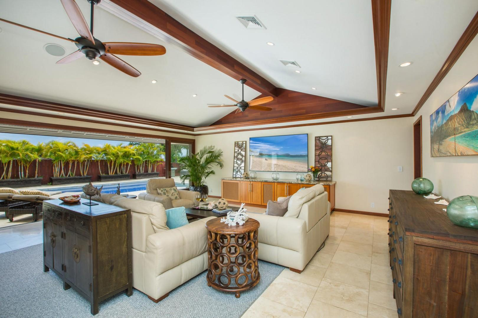 Enjoy the superior living room sound system with an 85-inch ultra-high-definition television, air conditioning, comfortable leather couches, and pool views.