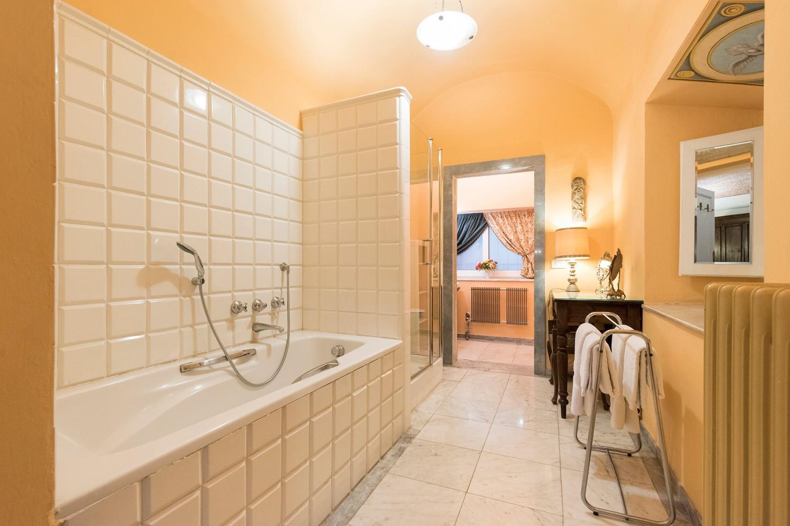 Bathroom 1 with bathtub, shower, toilet, sink.