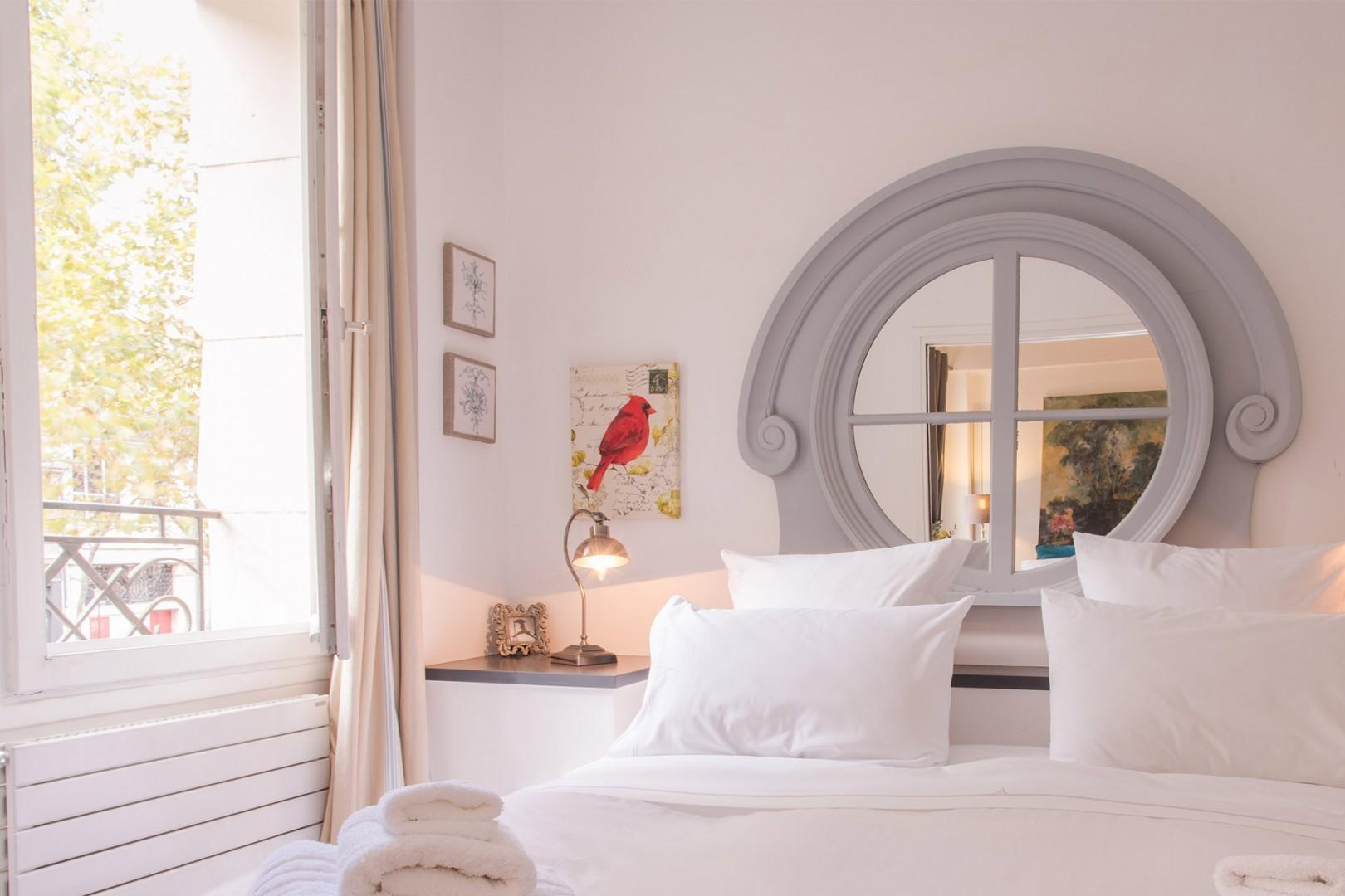 Large windows let lots of light into the lovely Parisian bedroom.