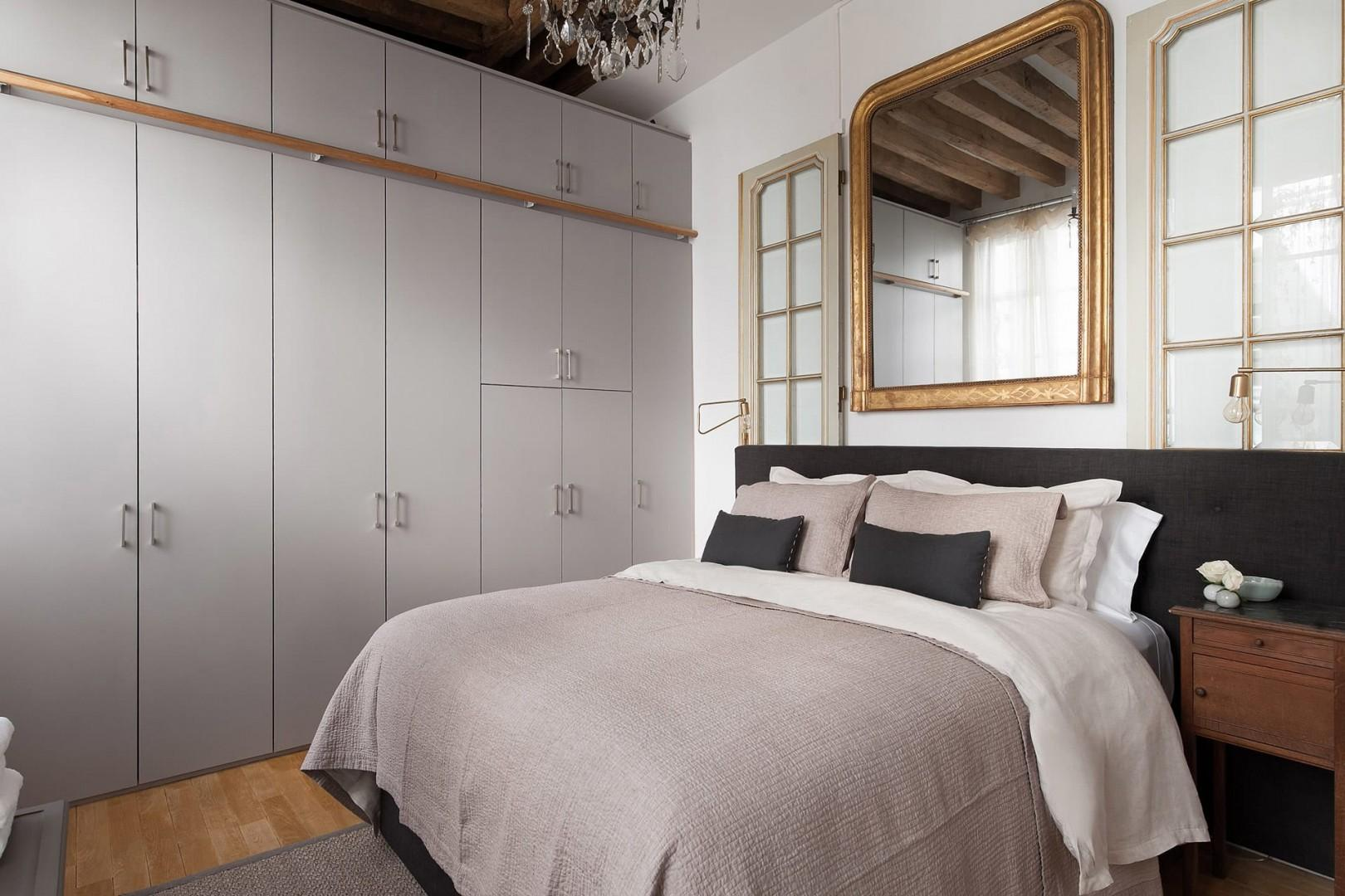 The bedroom features a large bed and a full wall of built-in closets.