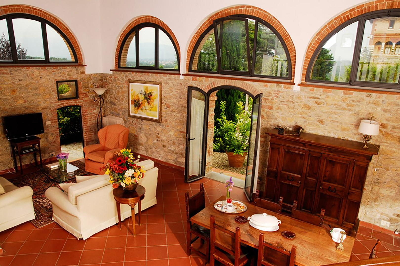 The high-ceilinged living room is filled with light from the arched windows on three sides.