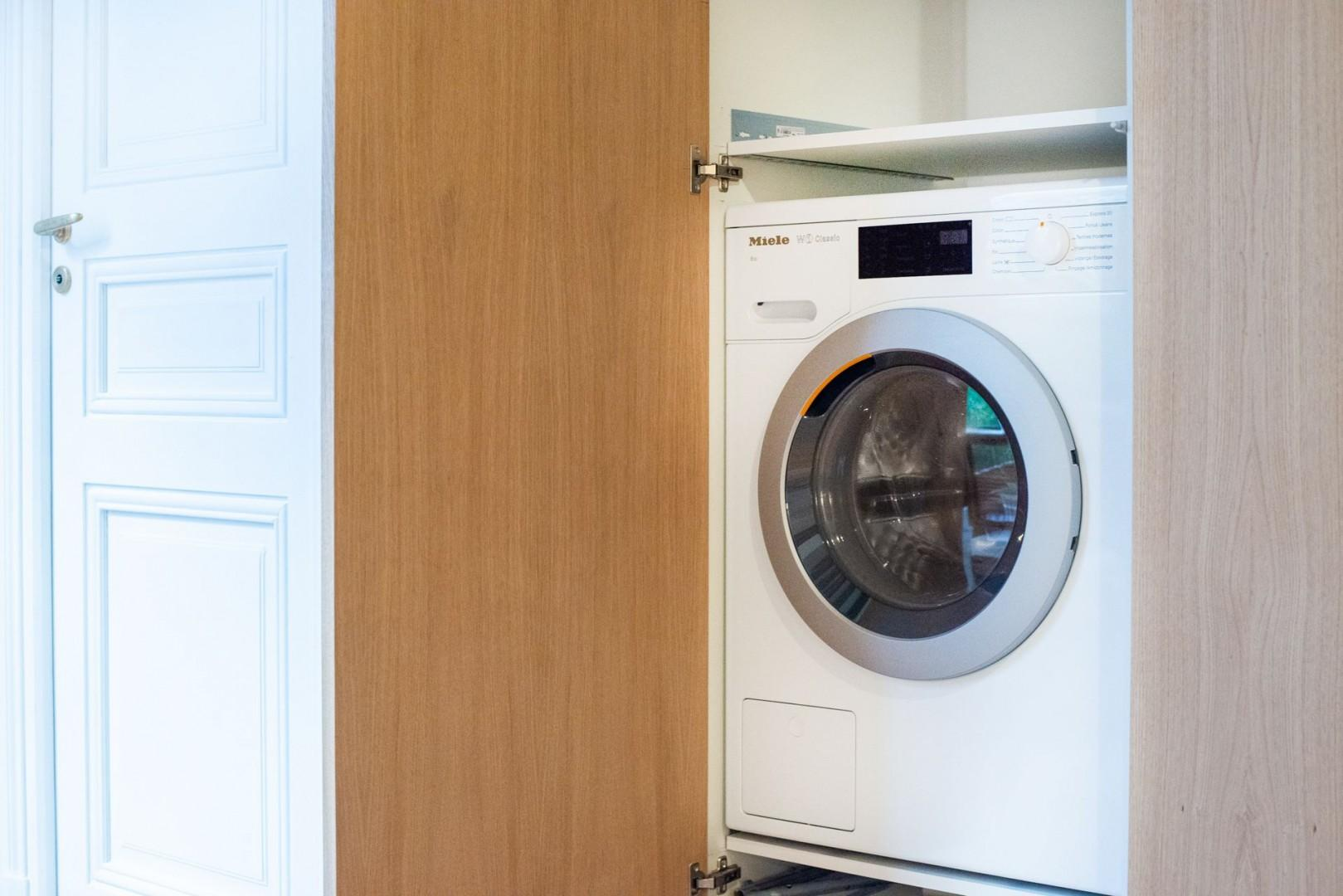 The closet hides a Miele washer and dryer.