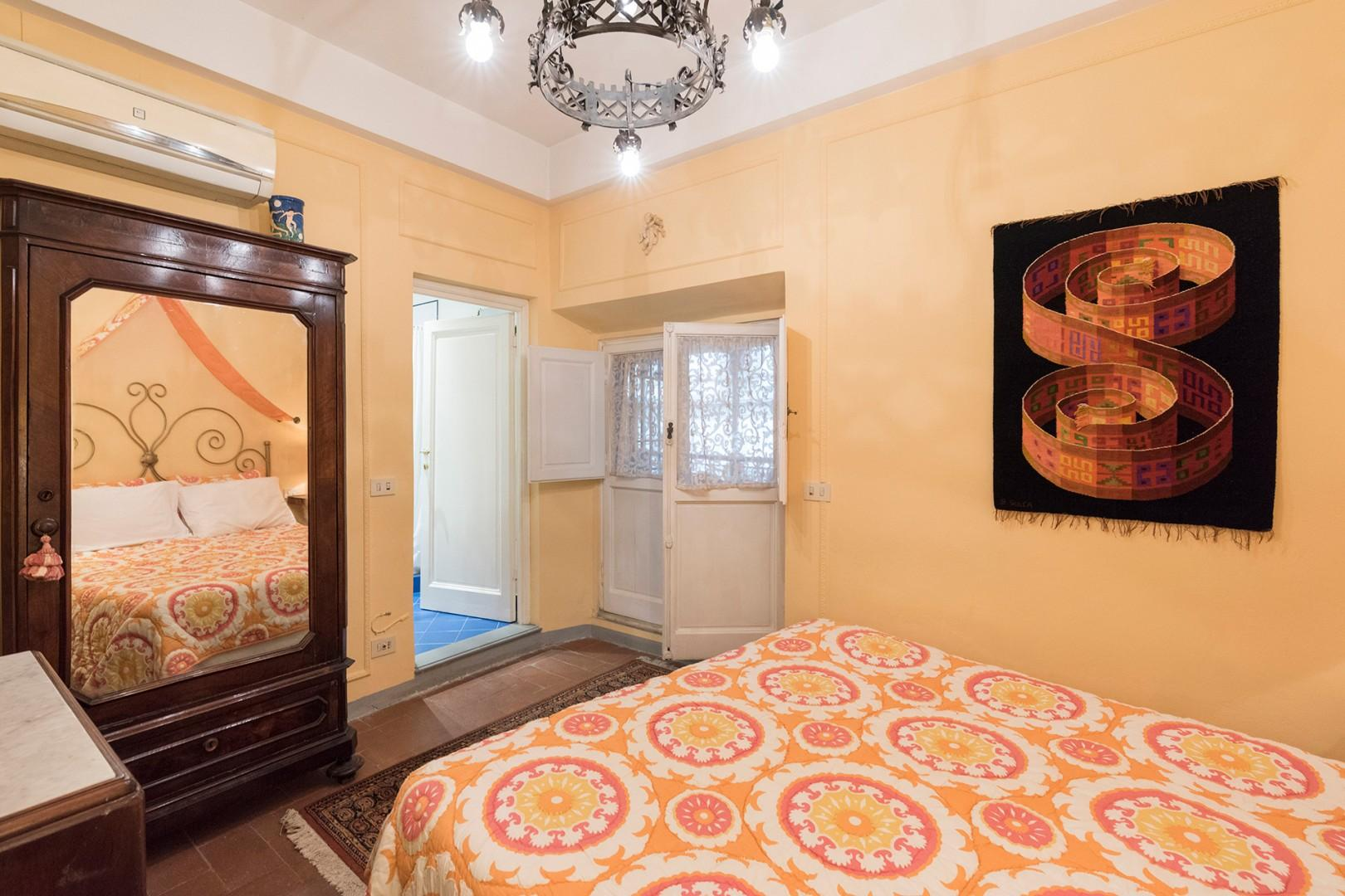 Sunny colors in the bedroom 2 with comfortable bed. The door opens to the terrace.
