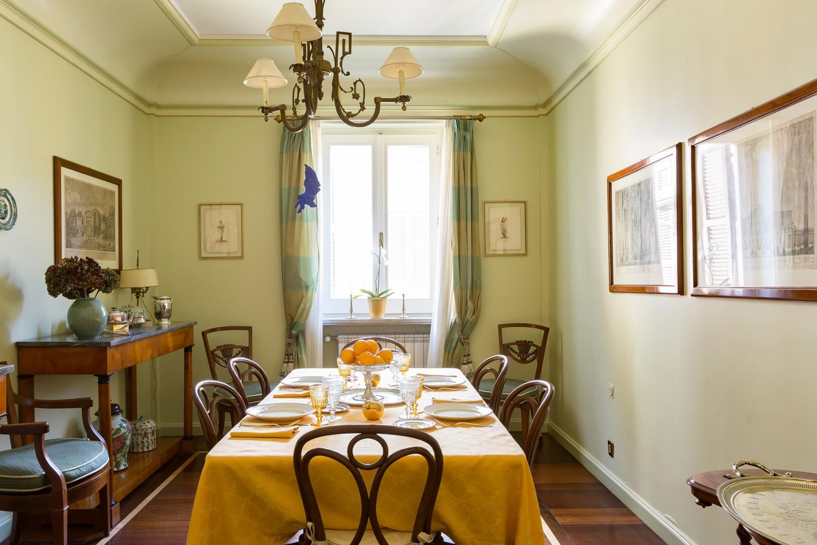 The formal dining room is beautifully furnished with antique sideboards and precious porcelain.