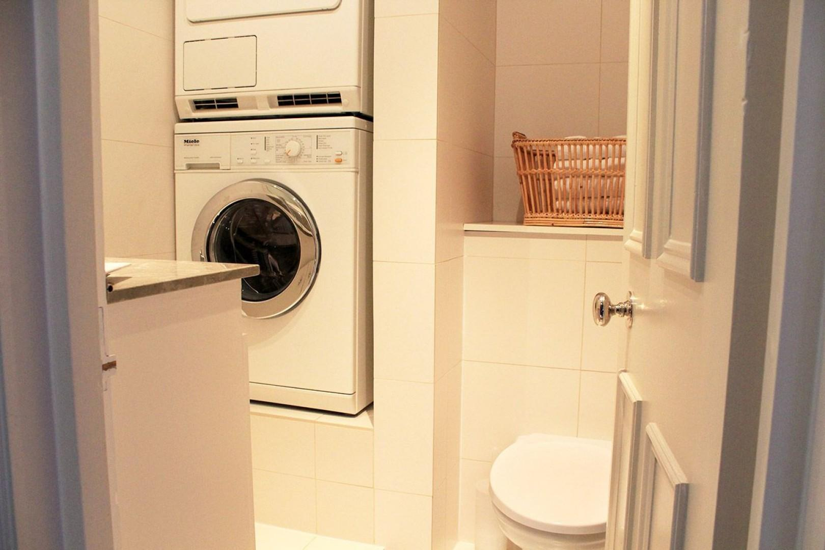 Separate half bath with toilet, sink, washer and dryer
