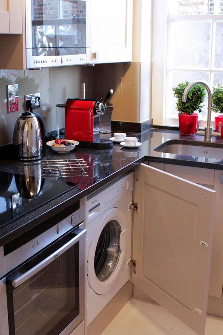Open cupboard in kitchen to find the washing machine