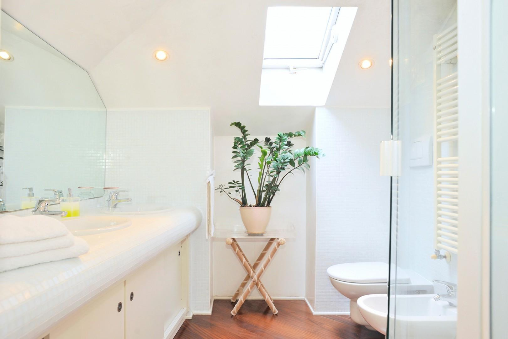 The compact bathroom with a double sink and a skylight that brightens.