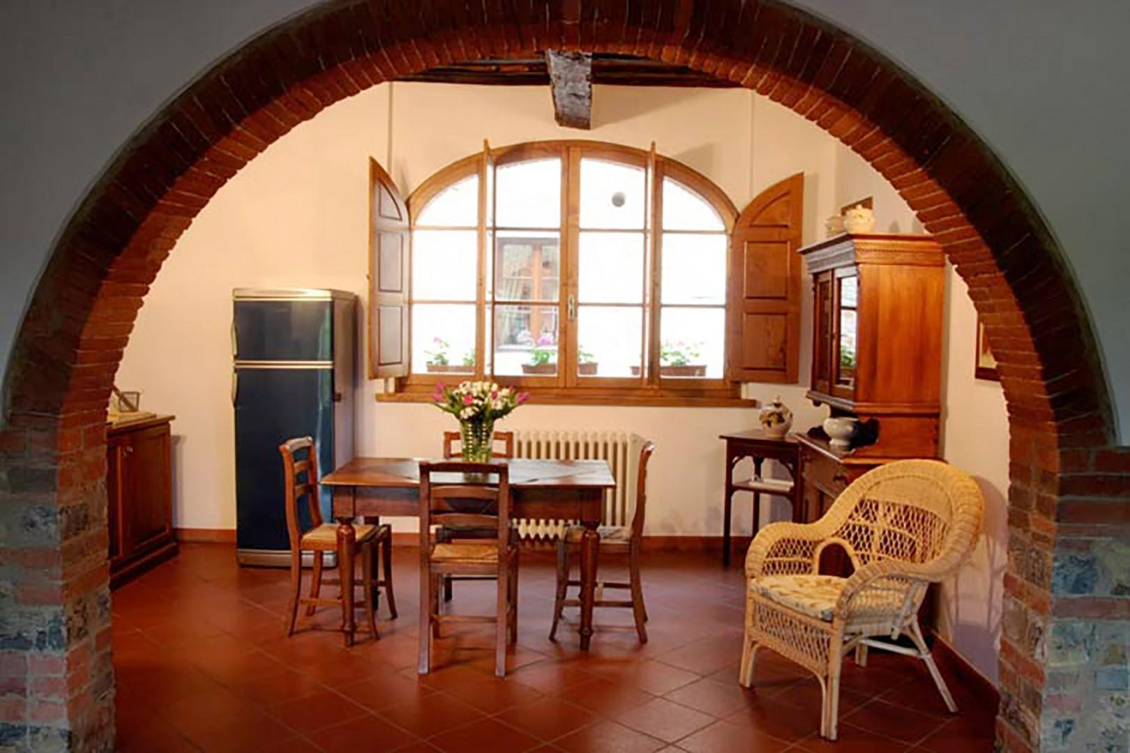An archway opens between the living room and the dining area with kitchenette.