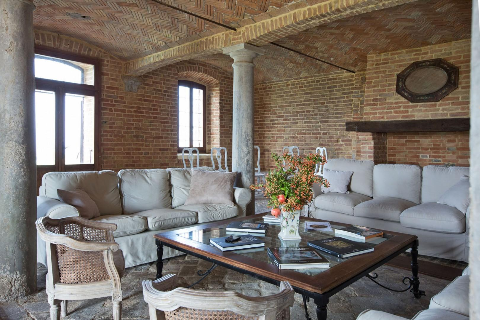 The spacious living room with brick arches and stone columns and lots of seating