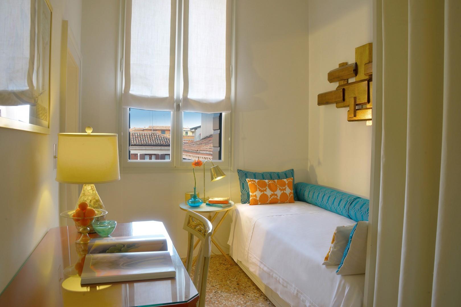 A door in bedroom 2 leads to bedroom 3 that has one bed.