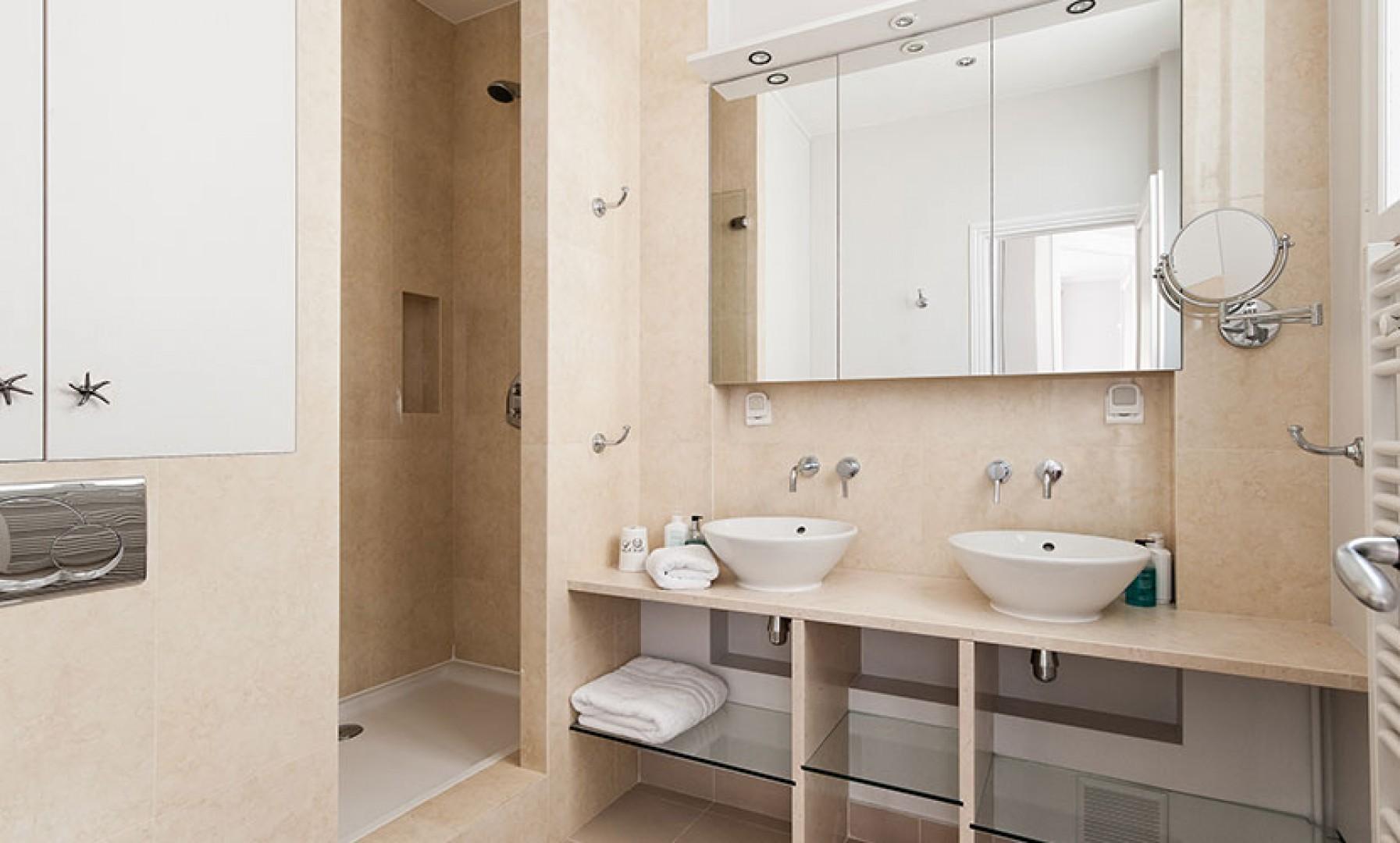 Bathroom 2 with shower, double sinks, toilet and heated towel racks