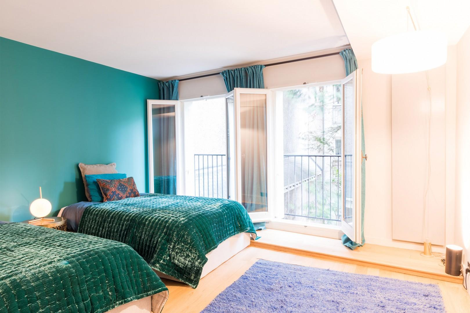 Two large French windows allow lots of natural light in bedroom 2.