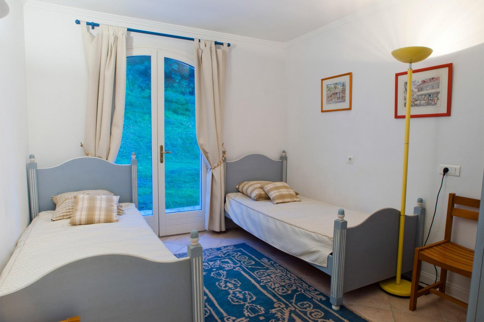 Bedroom three with two single beds and garden views
