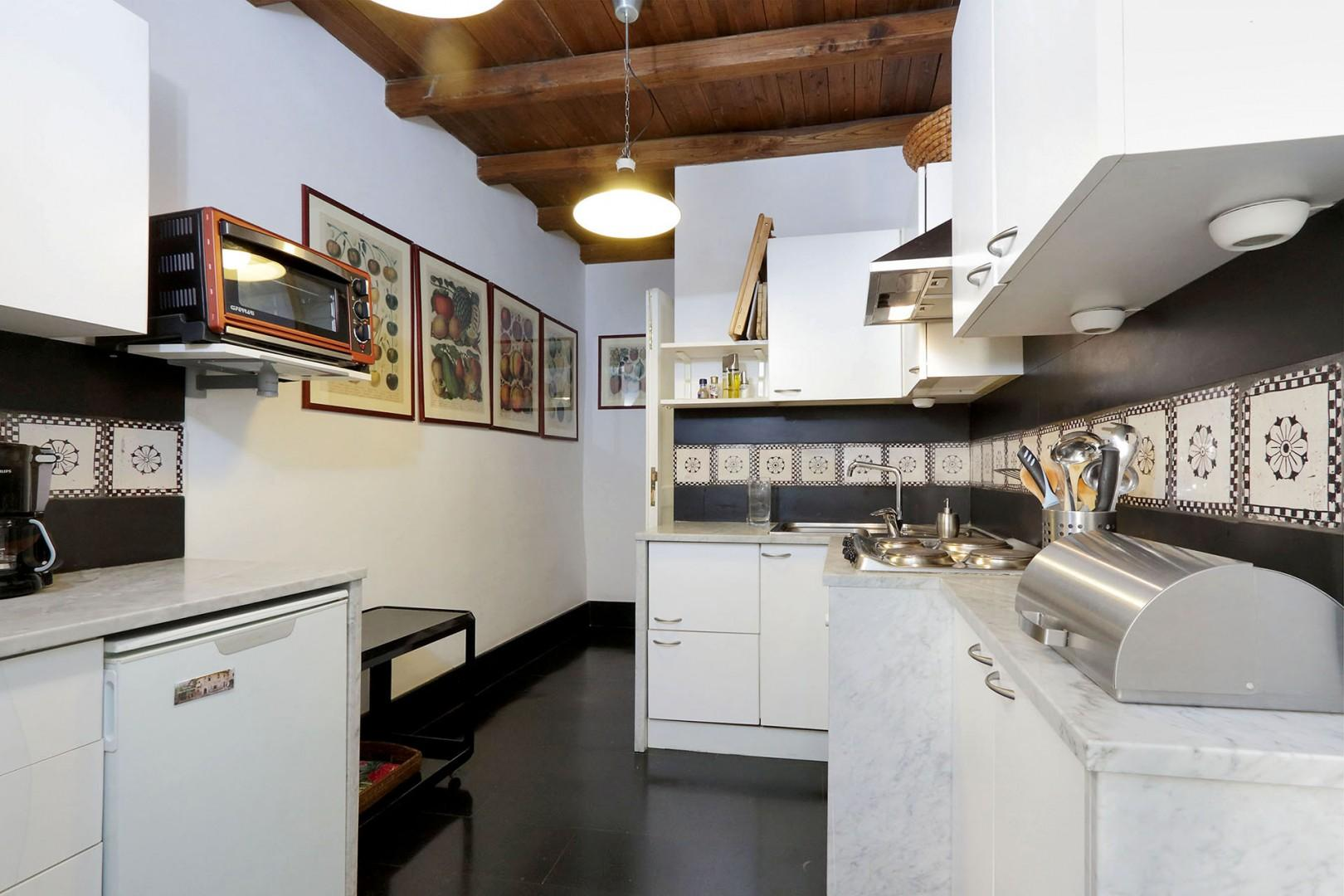 Colorful prints on the kitchen walls are echoed in the antique Italian tiles that line the walls.
