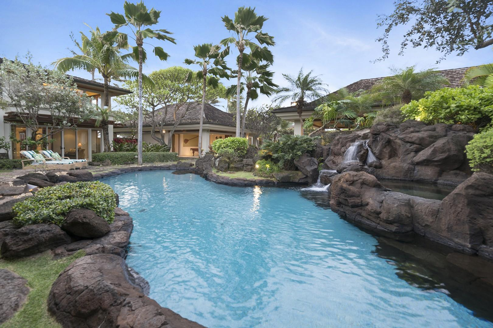Tropical lagoon style pool with natural rocks and cascading waterfalls.