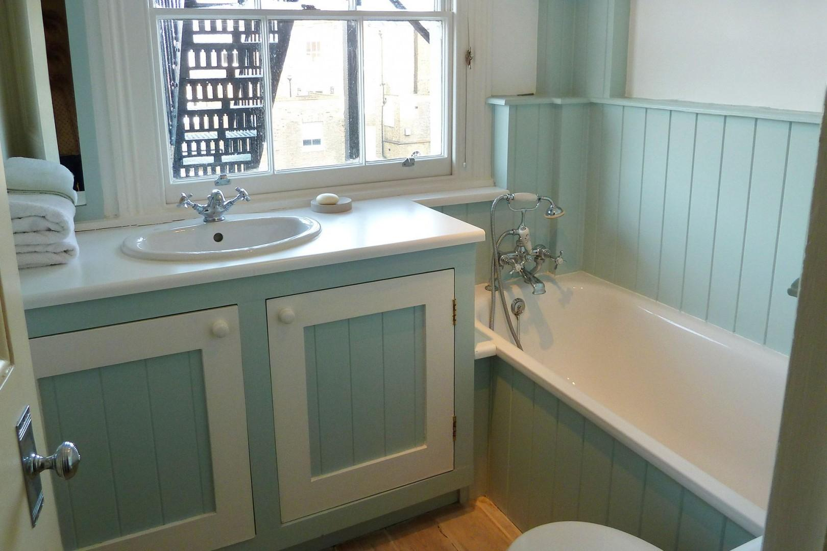 The third bathroom with bathtub, sink and toilet