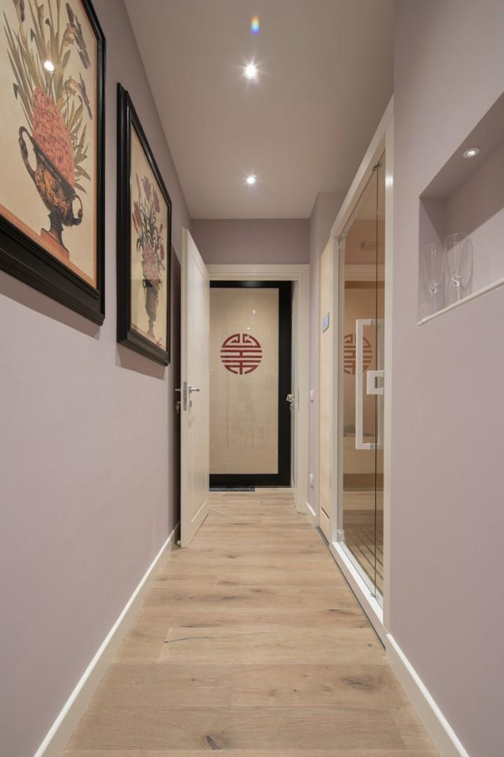 Well lit hallway with private sauna to your right.