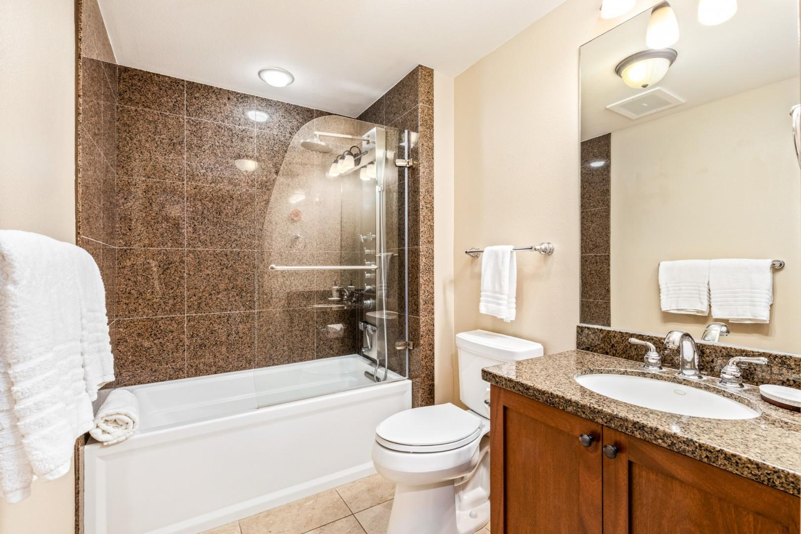 Full bathroom adjacent to guest bedroom with soaking tub/shower combo.
