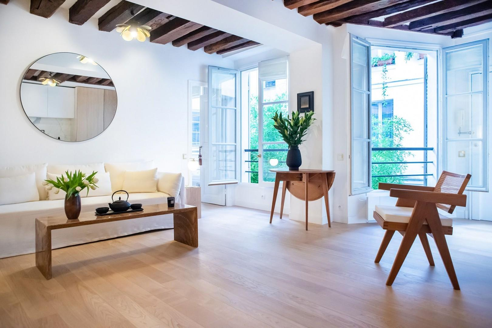 The bright and spacious living room has large French windows and high-end, modern furnishings.