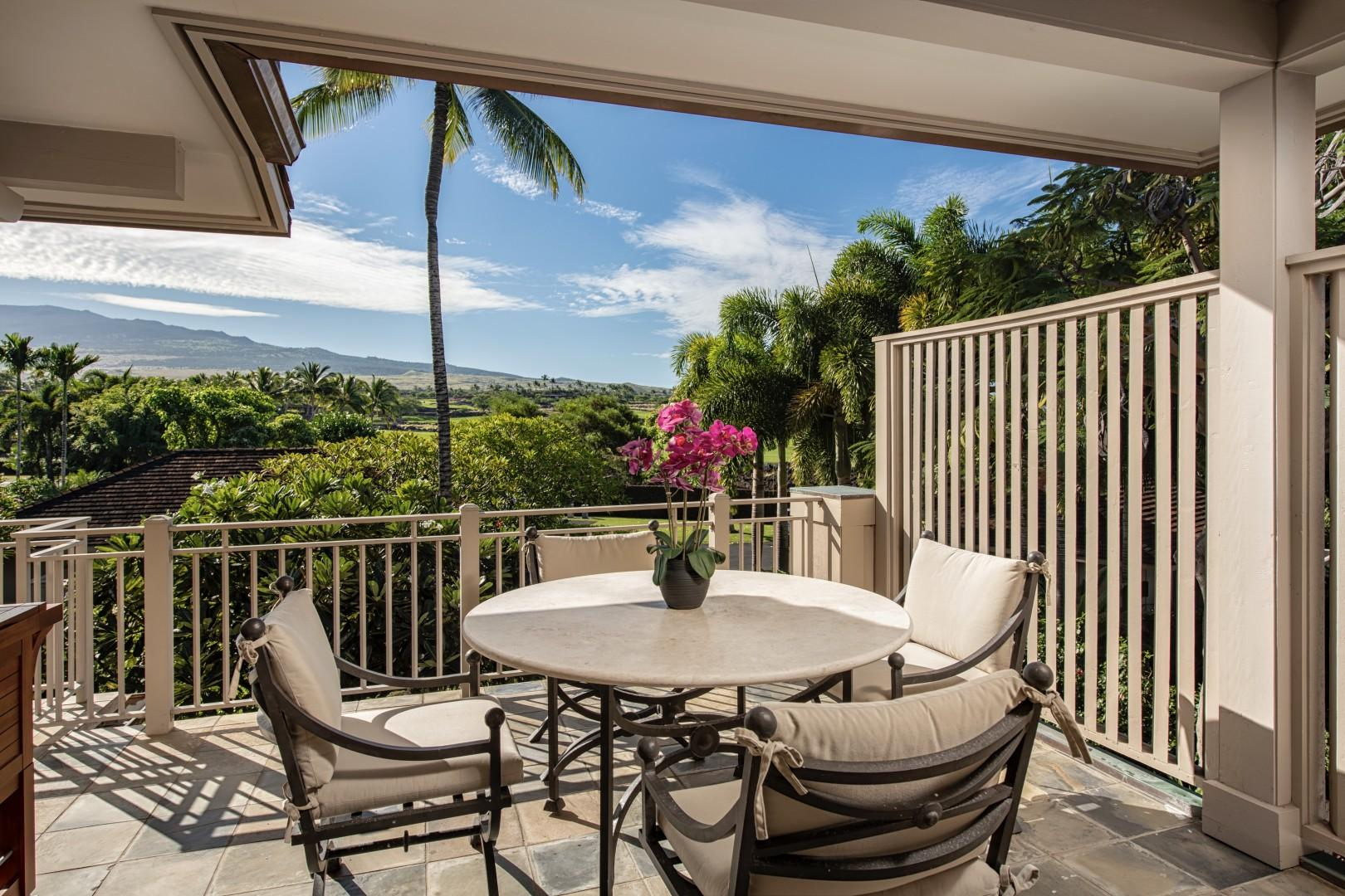 Outdoor patio off kitchen with breakfast table and view to Mount Hualalai.
