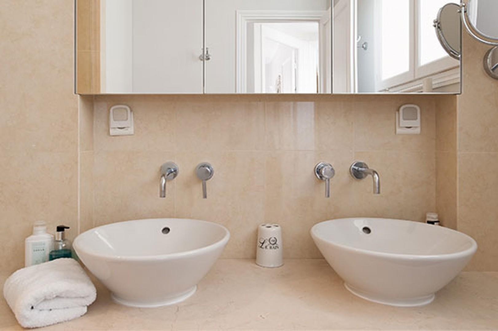Enjoy double sinks and plenty of storage space in bathroom 2.